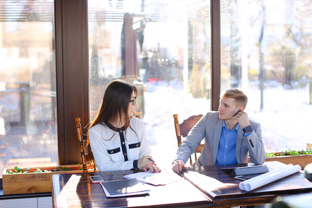 Pretty female secretary speaking with businessman at cafe and giving black document case. Young man sitting at cafe with beautiful woman in glasses. Concept of business meeting at catering establishment. Stok Fotoğraf