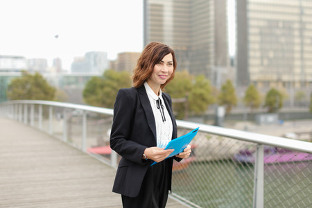 journalist, woman in business clothes go to work. Smiling middle-aged American lady wearing black jacket skirt and white blouse talking with friend on mobile. Concept of innovative technologies and gadgets or fashionable woman outfits. Stock Photo