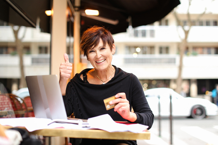 woman working at table with laptop and make purchases by credit card Stock Photo