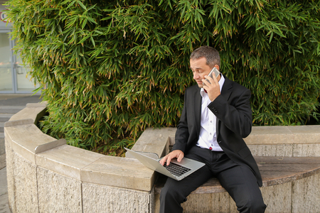 Male manager speaking by smartphone outdoors and working with laptop in  . Concept of modern technology, gadget and business  worker. Hardworking man wears black suit. Reklamní fotografie
