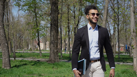 Arabian man walking in park with documents and laptop in hand. Guy dressed in black jacket and white jeans, blue shirt. Fellow has short dark hair and beard. Concept of places for rest clean parks and fresh air.