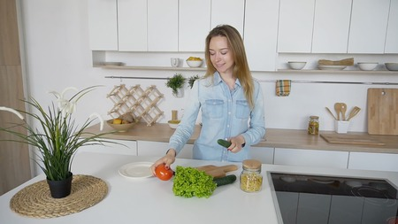 Housewife takes red tomato and green cucumber in hands, picks it up, and with smile on face thinks thoughtfully what to cook, looks and laughs at camera, standing in middle of stylish and white kitchen with various appliances for cooking food. Womens European appearance with light brown hair of medium length dressed in blue denim shirt and jeans. Concept of successful and happy people, balanced good nutrition, design and modern interior, technology and equipment for kitchen at home, promotion of healthy lifestyle. Stock Photo