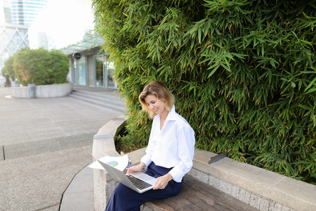 Female statistician working with color diagrams and laptop outdoors near green plant. Concept of working with theoretical or applied statistics. Young woman wears business clothes.