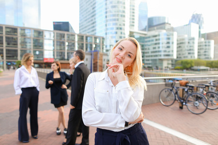 Blonde secretary looking at camera and playing with hair near talking employees background. Concept of businessperson and La Defense Paris. Young blonde woman is beautiful. Banque d'images