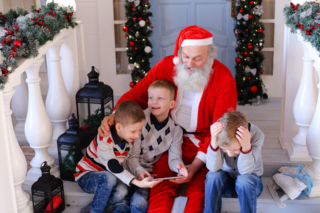 Father Christmas telling fairy tale for naughty boys about presents for good children and bad ones ( ). Man in red costume with beard entertains children gifting modern gadget. Concept of magic moments creating for kids. Фото со стока