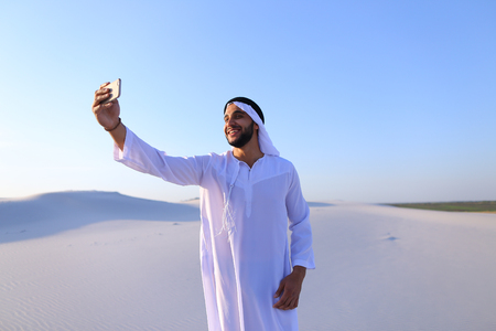 Happy, handsome guy, emirate and tourist, conducts dialogue through Internet with help of device, waves hand and smiles at camera of smartphone, shows beautiful views and sights of large sandy desert outdoors on summer day.