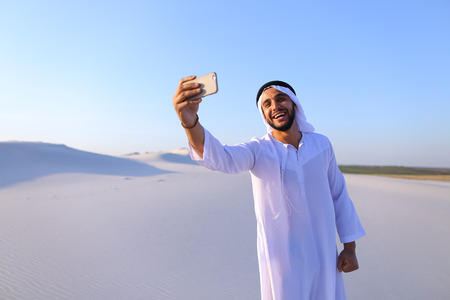 Happy, handsome guy, emirate and tourist, conducts dialogue through Internet with help of device, waves hand and smiles at camera of smartphone Stock Photo