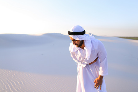 Worn-out Emirati man bends from pain and clings to stomach, suffers from severe pain and suffers with all strength