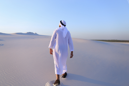 Charming young male Arab looks toward sun and goes up sand, examining landscapes of wide desert. Imagens