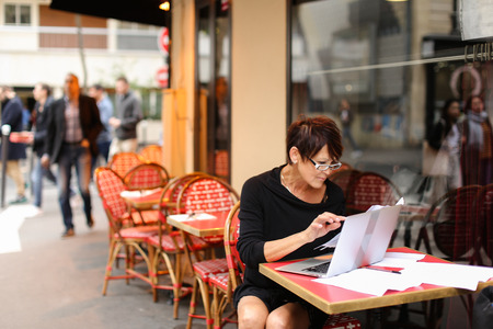 using laptop aged tired woman bank employee writing financial plan for several hours. Lady hold reports in left hand and printing last items in computer. Finishing, female wear glasses with contented expression on face, looks at results of work. Concept of laptop like indispensable professional tool.