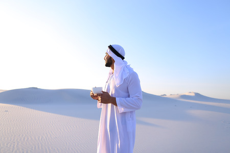 Portrait confident and happy male Muslim who drinks invigorating coffee drink from white cup and enjoys calm morning, standing in midst of endless sandy desert