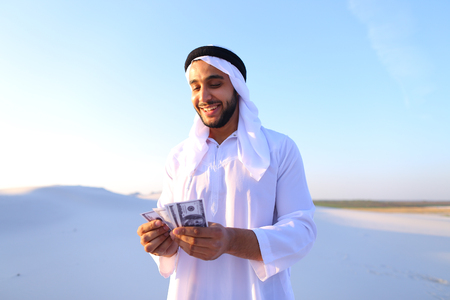 Handsome young Emirate in reckless mood recounts and examines banknotes