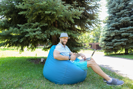 Gladden man sitting in bag chair and looking at camera with close up face near spruce. Handsome guy wears grey hat and t shirt