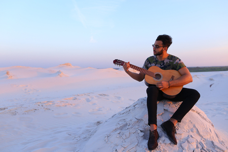 Bearded Muslim young man enthusiastically plays guitar and learns to take new chords or increases level of playing skills on musical