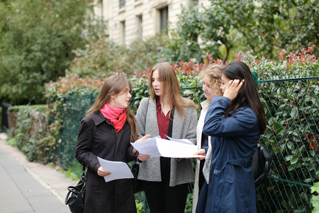 International student s with papers learning English near university building in  . Concept of learning language and education exchange programs.