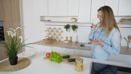 スマートフォンを手に持つかなり若い女性は、インターネット上の友人と対応し、手に紅茶やコーヒーの白いカップで立っています