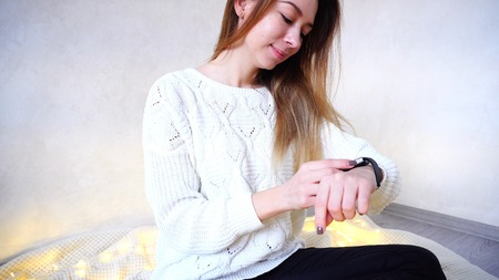 Portrait of beautiful Young Woman with gadget on hand, which moves fingers along small touch screen of modern smart watch watches, smiles and corresponds with friend online.