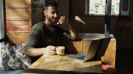 Young Muslim sits by table in modern cafe and drinks coffee. Bearded man with dimples laughing, looking at computer s screen.