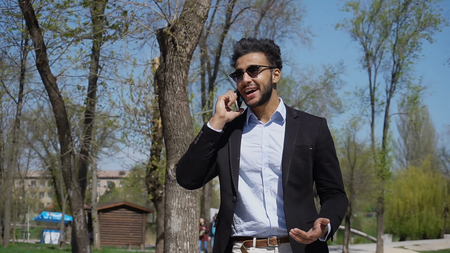 Young man holds in hand phone and talking. Arabian has dimples on cheeks, dark hair and beard. Guy wears black jacket, blue shirt and sunglasses. Concept of modern technologies free call work for young people well-paid job. Stockfoto