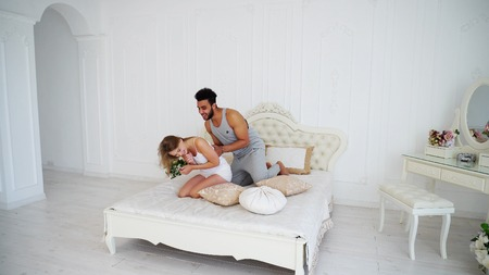 Funny and Charming Young Man and Woman in Love Laughing and Hugging. Male Easy to Tickle Women. Chic and Cozy Big Bed in Bright and Airy Bedroom