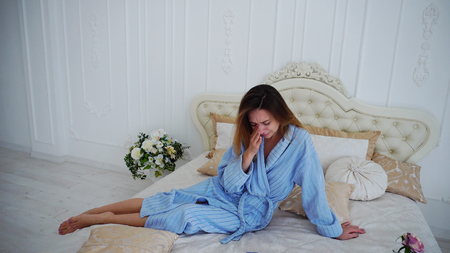 Girl Sits on Beautiful Double Bed and Sad, Crying Because of Failed Plans or Bad Day. Stock Photo