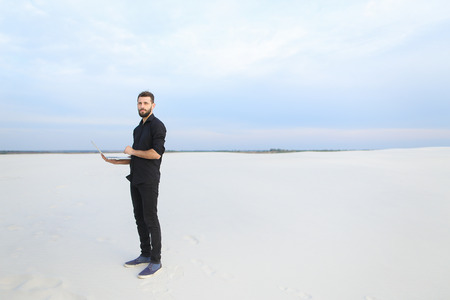 writer with laptop go to seaside, young man seek inspiration for book of travels. Bearded guy in black shirt standing among sands look around. Concept of innovative technologies, using gadgets for work or stylish clothes.