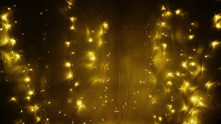 Twinkling yellow festoon. Switched fairy lights. Concept of indoor illumination for Christmas celebration.