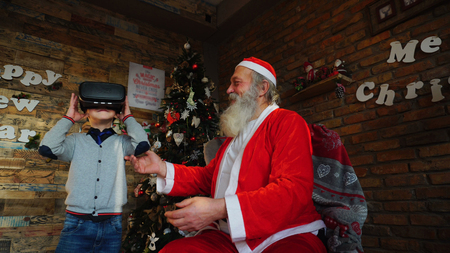 Small Canadian boy enthusiastically plays with virtual reality glasses. Kid with blond hair, gray sweater and blue jeans jumps and wag arms. Santa helps  to understand boy and holds child by hands. Concept of helping on holiday, enthusiasm for receiving gift, proper use and thrifty attitude.