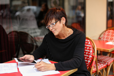 female designer sitting in outdoor cafe and waiting for order using tablet for viewing work of students.