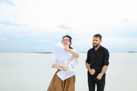future lawyers male and female come to seaside to have rest after passing exams, girl with ponytail in glasses tell good news friend bearded man with short fair hair. Young people wearing stylish outfits dancing for joy. Concept of fashionable clothes, modern accessories or beautiful landscapes.