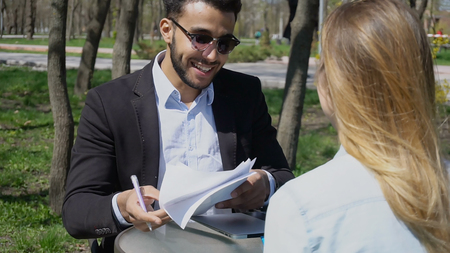 Seller talking with woman, bring documents and pan for signatures. People shake hands. Smiling man has dimples, dark hair and wears sunglasses. Woman has long fair hair and dressed in denim shirt. Concept of Internet advertising fast selling and agencies for sale.
