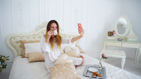 Marvelous Modern Women Photographing Themselves With Cup of Cafe on Camera Phone and Smiling. Young Woman of European Appearance With Long Fair Hair Below Shoulders Makes Photo to Social Networks or Send Morning Photo Lover in Robe Above Knee White With Transparent Inserts Into Flower Against White Wall in Large Elegant Bedroom and Sits on Soft Comfortable Beige Bed Beside Which Stands Table With Mirror and Chair. Concept of Beautiful and Successful Young People, Technology and Photography For Social Networks, Well-Groomed Wife and Housewife, Advertising Lingerie and Cosmetic Products, Wealthy and Luxury Apartments.