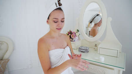 Delicate Girl With Beautiful Skin Cream Applied to Face and Beauty Treatments After Shower. Woman Sitting at Table on Which Stands Casket, Flowers and Perfume, Smiling Into Mirror and Happy Skin Condition in Large Towel and Small Body Wrapping Head. Concept of Well-Groomed Girl, Healthy and Beautiful Slim Figure, Advertising of Cosmetics For Face, Bath Rest and Relaxation Care of Your Body and Freshness After Shower.