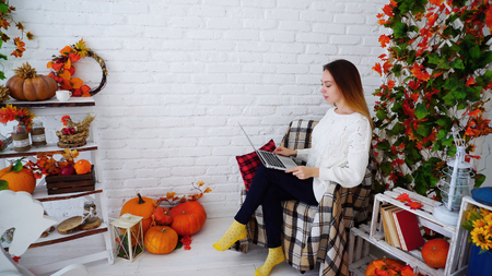Cute and Confident Young Woman Doing Work on Errors and Recheck Adjustments in Control Work, Sitting With Black Folder in Hands on Chair Sheltered Plaid on Background of White Brick Wall in Background Scenery, Pumpkins and Foliage, Flowers and Autumn Vegetables, Raises Head, Smiling and Looks in Camera.student Girl of European Appearance With Long Brown Hair Wearing Light Knitted Sweater, Dark Trousers and Bright Yellow Socks. Concept of Modern Technologies and Successful Smart People, Education and Social Life, Homework or Work Online. Standard-Bild - 97329988