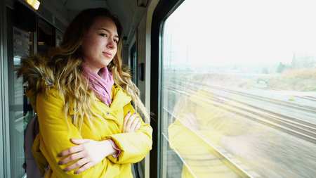 Alluring girl travels in train, makes sad face and weeps, mourns that she leaves beloved city and looks out  window after  flashing scenery in  street in  autumn afternoon. European-looking girl with long blond hair smiles and looks at  camera and dressed in fluffy warm yellow coat with backpack on shoulders and pink scarf.  Concept of active people and travel,  road and traffic in railway vehicles,  autumn and  cold season.