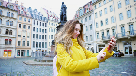 Portrait of pleasing Young woman who holds smartphone and communicates online in videocall with parents and takes pictures of architecture of old European city Dresden. Stock Photo