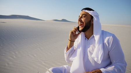 Smart handsome emirate Arabian UAE Sheikh businessman prints on computer keyboard and answers incoming phone call from business partner or client, communicates about building in desert. Young Arab smiles and sits on white clean sand outdoors on hot summer day. Swarthy Muslim with short dark hair dressed in kandura, long, spacious dress made of white unpainted cotton with knitted lace cap of hafia, on top of which headscarf and dark brown shoes are tied. Concept of Arab and Muslim men, business and business, modern technology and gadgets, united Arab emirates and beautiful landscapes, sheikh in desert and seclusion from nature, national clothes of emirates. Stock Photo