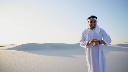 Handsome male Muslim sends message to friend using modern smart watch device, which worn on hand and shares impressions of what he saw, smiles and looks at landscapes of large sandy desert against blue sky on hot summer morning. Swarthy Muslim with short dark hair dressed in kandura, long, spacious dress made of white unpainted cotton with knitted lace cap of hafia, on top of which headscarf and dark brown shoes are tied. Concept of Arab and Muslim men, business and business, modern technology and gadgets, united Arab emirates and beautiful landscapes, sheikh in desert and seclusion from nature, national clothing of emirates.