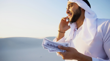 Arab young sheikh calls to friend or business partner and with smile on face and joy in eyes tells about winnings and amount of money in hands, rejoices and recounts bills standing in middle of bottomless desert with white sand on sunny summer day. Swarthy Muslim with short dark hair dressed in kandura, long, spacious dress made of white, unpainted cotton with knitted lace cap, gafia, over which headscarf tied. Concept of Arab and Muslim men, business and finance, modern technology and gadgets, United Arab Emirates and beautiful landscapes, national clothes of emirates. Stock Photo