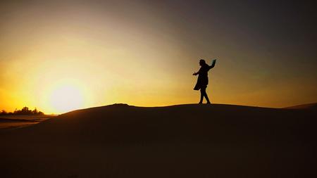 堂々とアラブ人の男が歩いて、小さな砂の丘を登ります。人間は手にフォルダや書類を運び、手を横に広げ、日没時の砂漠の美しさを賞賛し、夏の