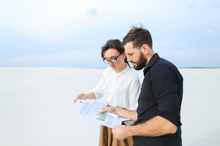 Landscape designer woman come to customer s new house to show sketches, people standing outdoors discussing designs. Fair-haired female in glasses without makeup demonstrating papers to bearded concentrated guy. Concept of stylish clothes, homestead planning or draft of grounds.