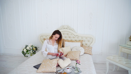 Lovely Modern Young Woman Watching Womens Magazine, Noting For Themselves Something Useful or Read Gossip Show Business. Light Brown Girls Doing All Household Chores, Sat Down to Rest on Large Beige Bed and See Magazine, Placing Themselves Near Gray Tray With Cup and Saucer, Biscuits and Vase With Flower, Dressed in Robe Above Knee White With Transparent Inserts in Flower. Concept of Beautiful and Successful Young People, Independent Life and Responsibility, Well-Groomed Wife and Housewife, Womens Magazines on Variety of Topics, Advertising Lingerie and Cosmetic Products, Wealthy and Luxury Apartments. Stock Photo