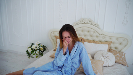 Girl Sits on Beautiful Double Bed and Sad, Crying Because of Failed Plans or Bad Day. Womens European Appearance With Long Fair Hair Dressed in Long Robe of Blue Stripes and Sits on Big Soft Beige Bed Among Pillows in White Room, Spacious Bedroom. Concept of People and Sad Emotions, Unfulfilled Dreams and Hopes, Black Stripe in Life. Фото со стока