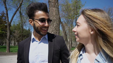 Couple discussing themes and laughing. Caucasian girl has long fair hair, white teeth and dressed in white T-shirt and denim shirt. Muslim boy has black hair, beard, dimples on cheeks and wears sunglasses. Concept of online dating websites communication.
