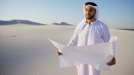 Beautiful Emirate Sheikh businessman studying project of future construction of complex, standing in middle of bottomless desert with white clean sand on clear warm day against blue sky. Swarthy Muslim with short dark hair dressed in kandura, long, spacious dress made of white unpainted cotton with knitted lace cap of hafia, on top of which headscarf and dark brown shoes are tied. Concept of Arab and Muslim men, business and business, United Arab Emirates and beautiful landscapes, sheikh in desert and seclusion from nature, Emirates national costume.