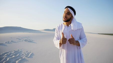 Portrait of Muslim Arabian Sheikh  male sales representative who with friendly look and smile on face actively advertises information or goods, gestures and makes deal, shakes hands with hand from camera, standing in middle of bottomless sandy desert with white clean sand against blue sky with hot day outdoors . Swarthy, handsome Muslim with short dark hair dressed in kandura, long, spacious dress made of white unpainted cotton with knitted lace cap of hafia, on top of which tied goutrail and dark brown shoes. Concept of Arab and Muslim men, United Arab Emirates and beautiful landscapes, advertisement of travel company or airline advertising, national clothes of Emirates, good mood and happy emotions.