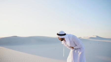 Worn-out Emirati man bends from pain and clings to stomach, suffers from severe pain and suffers with all strength, standing in midst of bottomless desert with snow-white sand on sunny summer day. Swarthy Muslim with short dark hair dressed in kandura, long, spacious dress made of white, unpainted cotton with knitted lace cap, gafia, over which headscarf tied. Concept of Arab and Muslim men, United Arab Emirates and beautiful landscapes, advertisement of pharmaceuticals and medicines, deteriorated state of health and prevention of treatment of diseases, national clothing of Emirates.