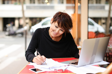 middle aged female student using laptop for writing a research work. Woman sitting at red table in cafe and writing information from internet article. Lady looks enthusiastic about work. Concept of study with modern gadgets. Stock Photo