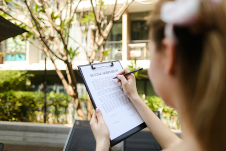 girl travel and rent short term condo in europe. concept of traveler looking for place to live sunny day, focus on doc. close up portrait of woman hands signing rental agreement on background of leasing office apartments. Front used with Open Font License
