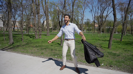Boy dancing, twist and throw jacket over shoulder. Man dressed in blue shirt, white jeans and brown shoes. Boy has black hair and beard. Concept of agency for selection of work well paid job. Stockfoto